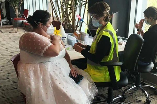 Woman wears wedding dress for vaccination